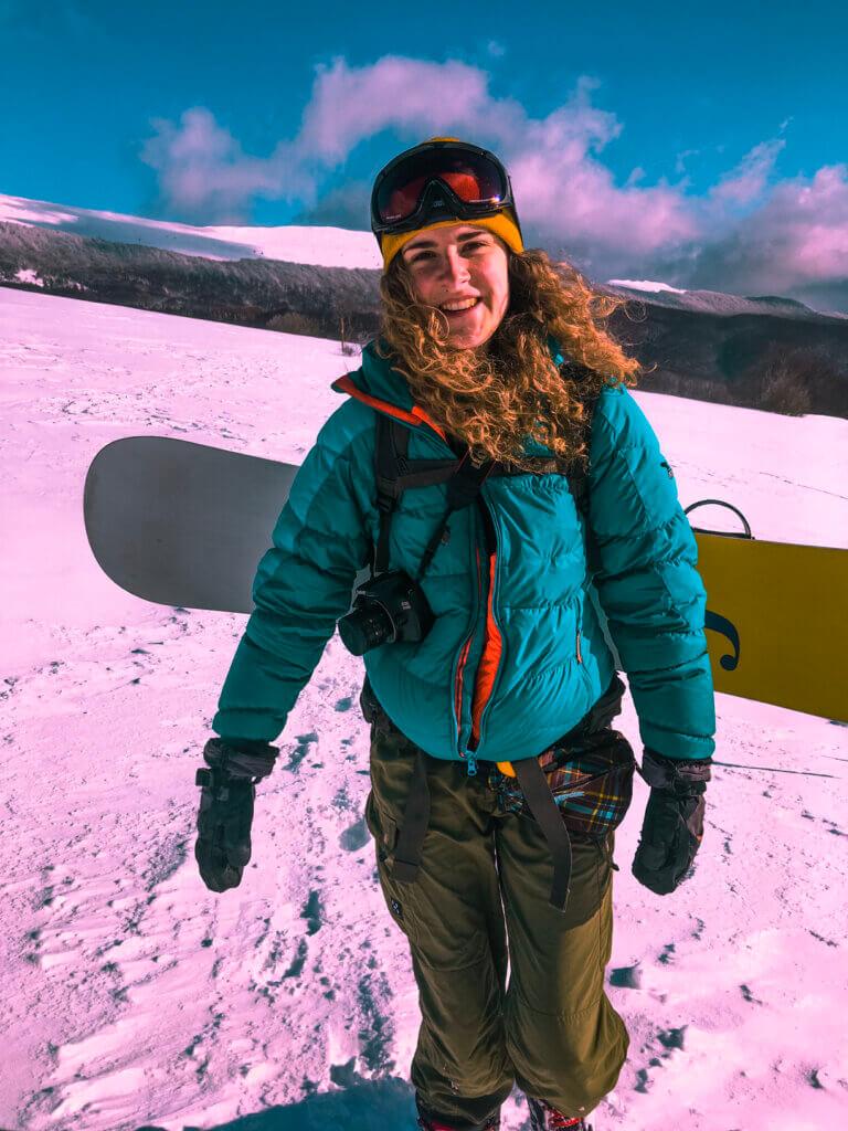 dziewczyna ze snowboardem w górach na śniegu